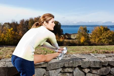 haciendo ejercicio: Una hermosa mujer cauc�sicos hacer ejercicio al aire libre en un parque