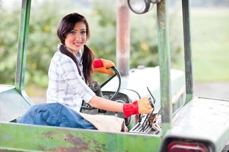 A shot of a girl riding a tractor in a farm
