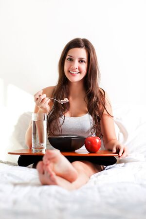 A shot of a beautiful girl eating breakfast in bed photo