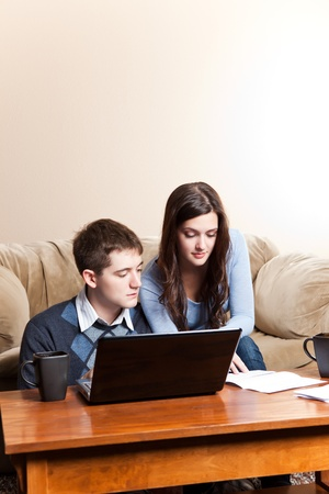 A couple paying bills by using online banking at home photo
