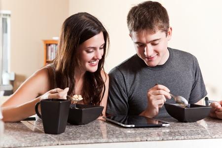 pareja comiendo: Un tiro de una joven pareja de comer el desayuno y la lectura en tablet PC