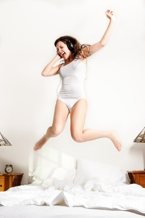 A shot of a beautiful girl jumping on the bed listening to music Stock Photo - 8436995
