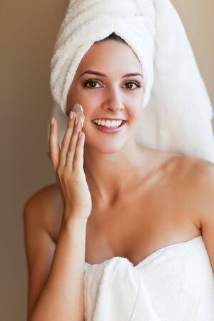 A shot of a young beautiful woman applying lotion to her face photo