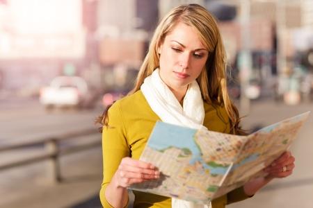 Un tiro de una hermosa mujer itinerante del Cáucaso leer un mapa Foto de archivo