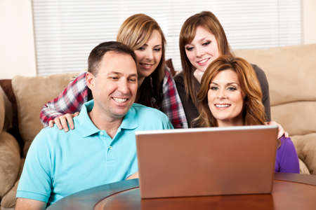 A shot of a caucasian family browsing internet on the laptop at home photo