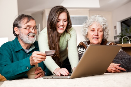 A portrait of a happy senior couple shopping online with the help from their granddaughter Stock Photo - 8638161