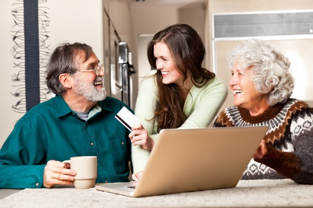 A portrait of a happy senior couple shopping online with the help from their granddaughter photo
