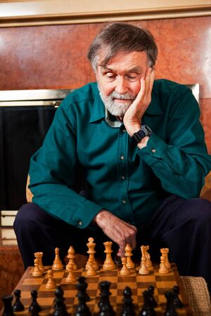 A portrait of a senior caucasian man playing chess photo