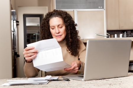 A shot of a middle age caucasian woman paying bills at home photo