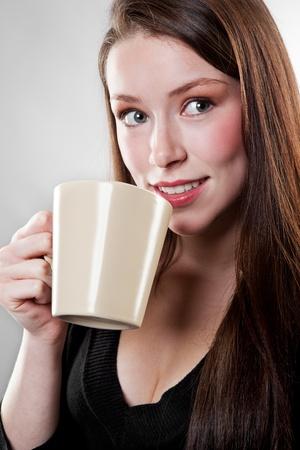 A shot of a beautiful caucasian businesswoman drinking coffee photo