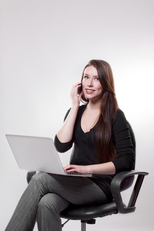 A beautiful caucasian businesswoman talking on the phone while working on her laptop Stock Photo - 8712494
