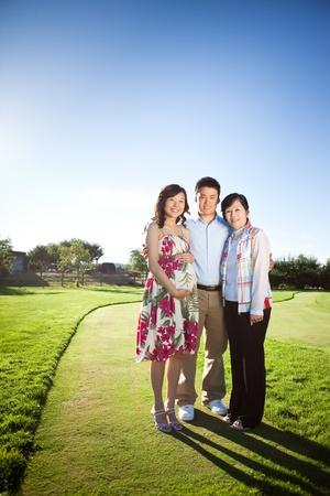 그녀의 남편과 그녀의 어머니는 야외 임신 아시아 여자의 초상화 스톡 콘텐츠