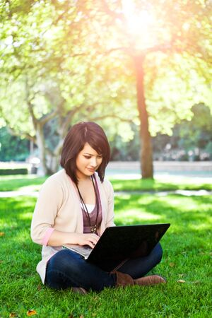 Mixed race college student sitting on the grass working on laptop at campus 版權商用圖片