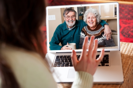 senior ordinateur: Un coup d'une vid�oconf�rence couple de personnes �g�es avec leur petite-fille