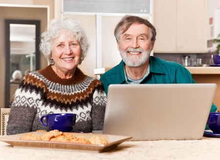 A portrait of a happy senior couple using computer at home photo