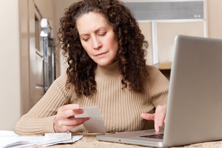 A shot of a middle age caucasian woman paying bills at home Stock Photo - 8809497