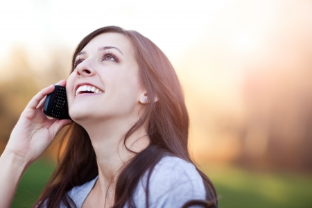 A portrait of a smiling beautiful woman talking on the phone Stock Photo - 8809743