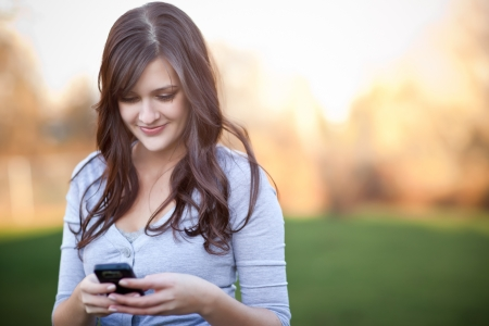 A portrait of a smiling beautiful woman texting with her phone photo