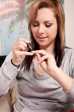 10 代の少女が彼女の自宅で彼女の爪を研磨のショット