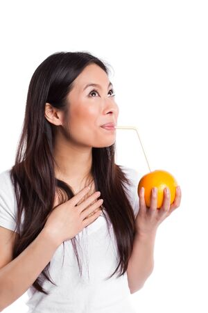 An isolated shot of a beautiful asian woman drinking orange juice photo