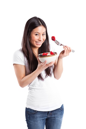 An isolated shot of an asian woman holding a bowl of fruit