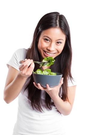ni�a comiendo: Un disparo aislado de una mujer asi�tica sosteniendo un taz�n de ensalada