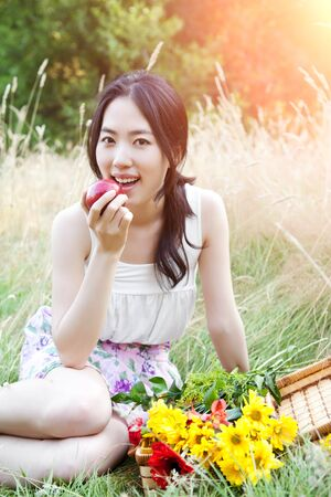 A portrait of a beautiful asian woman eating an apple outdoor photo