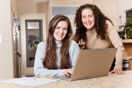 A happy teenage girl and her mother using laptop at home photo