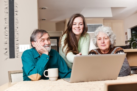 A happy teenage girl and her grandparents using a laptop