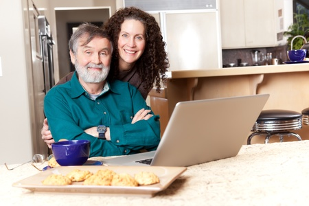 A senior father with his middle age daughter using a laptop photo