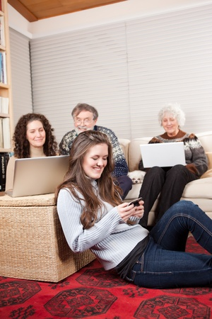 A family at home using wireless technology such as laptop and cell phone photo