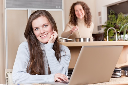 A happy teenage girl using laptop at home while her mother cooking in the kitchen photo