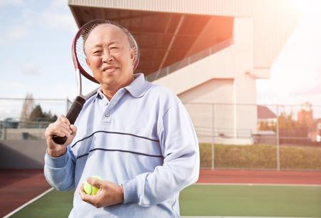 tennis stadium: Un disparo de un hombre asi�tico senior jugando tenis