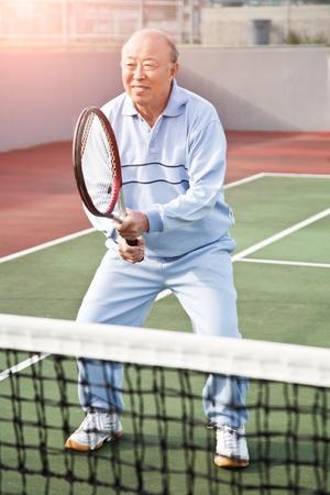 Een schot van een senior Aziatische man met tennis