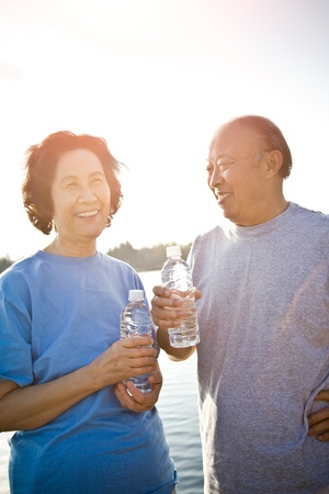 A shot of a happy senior asian couple chatting after a workout Foto de archivo