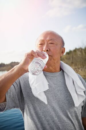 70s adult: An active senior asian man drinking water after exercise Stock Photo