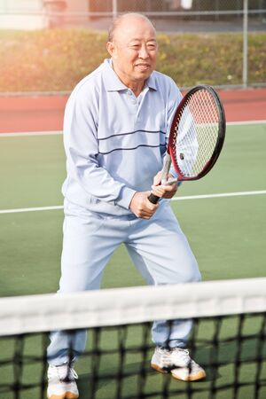 A shot of a senior asian man playing tennis photo