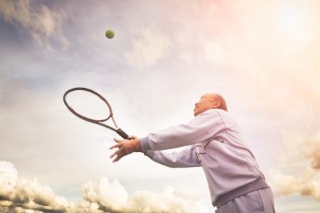 personnes �g�es: Un projectile dun homme asiatique a�n� jouant au tennis