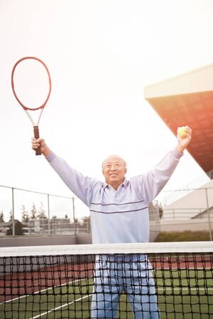 70s tennis: A shot of a happy asian senior tennis player playing tennis Stock Photo