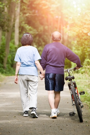 A couple senior asian talking while walking and exercising at a park photo