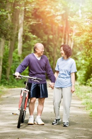 A couple senior asian talking while walking and exercising at a park Stock Photo