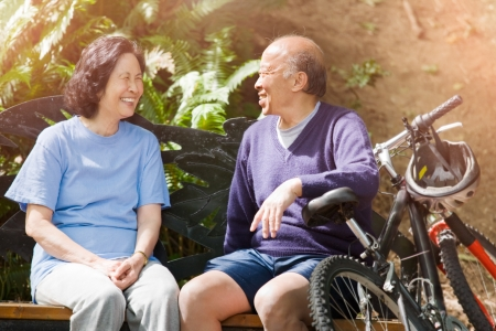happy asian couple: A shot of senior asian couple sitting on a bench at a park Stock Photo