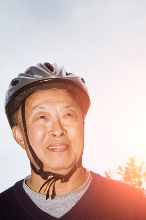 A shot of a senior asian man wearing a bike helmet photo