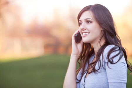 A portrait of a smiling beautiful woman talking on the phone photo