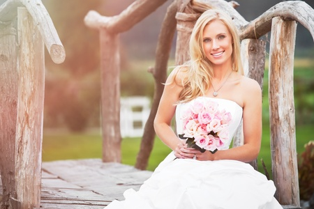 A shot of a beautiful caucasian bride sitting outdoor photo