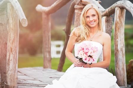 A shot of a beautiful caucasian bride sitting outdoor photo