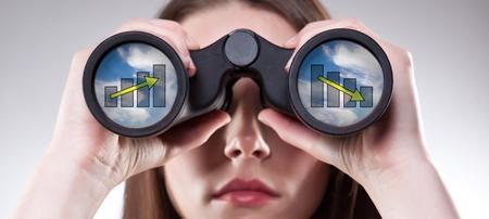 Una empresaria mirando a través de binoculares, ver las tendencias contradictorias en la predicción de ingresos, puede utilizarse para la visión de negocios o concepto de predicción de negocio Foto de archivo