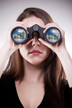 A businesswoman looking through binoculars, seeing conflicting trends in earnings prediction, can be used for business vision or business prediction concept 版權商用圖片