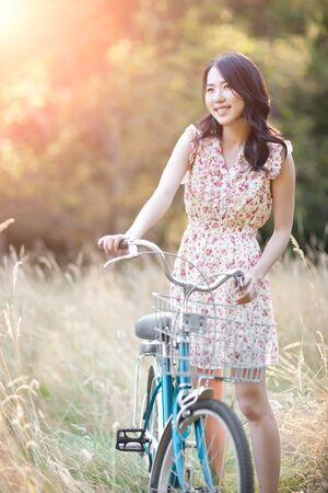 korean fashion: A portrait of a beautiful asian woman with a bicycle outdoor