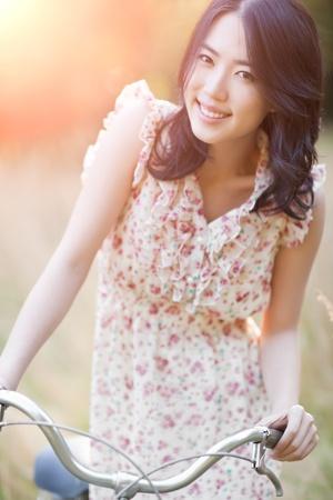 korean fashion: Un retrato de una hermosa mujer asi�tica con una bicicleta al aire libre Foto de archivo